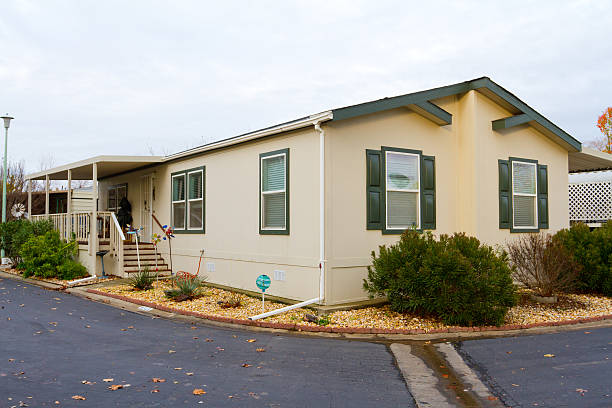 One story manufactured house with gravel and driveway A new manufactured home at a retirement trailer park. manufactured housing stock pictures, royalty-free photos & images