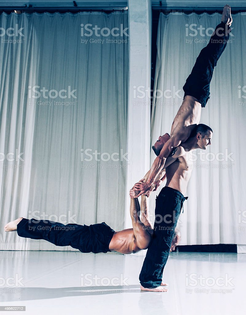 One strong acrobat holds two other men above the ground stock photo