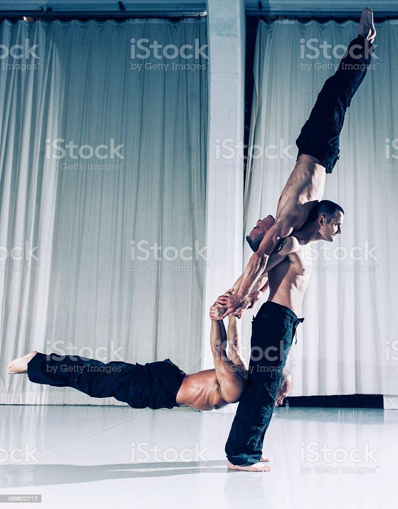 Eine starke acrobat für zwei Männer über den Boden – Foto