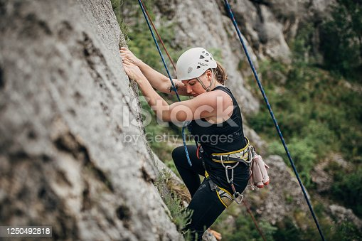 One young woman, free climber, with a rope climbing on the rock mountain in nature.