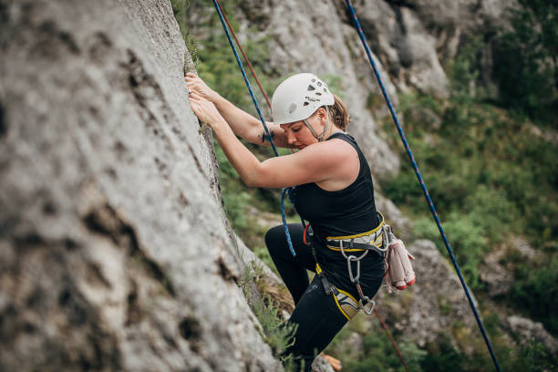 One strong young climber woman climbing on the rock stock photo
