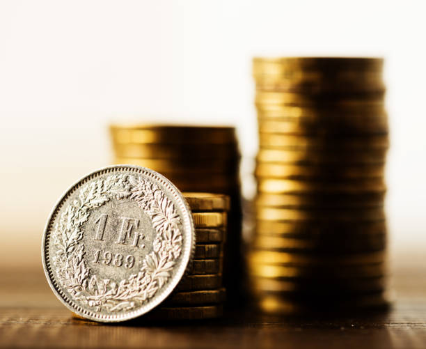 one swiss frank coin and gold money on the desk stock photo