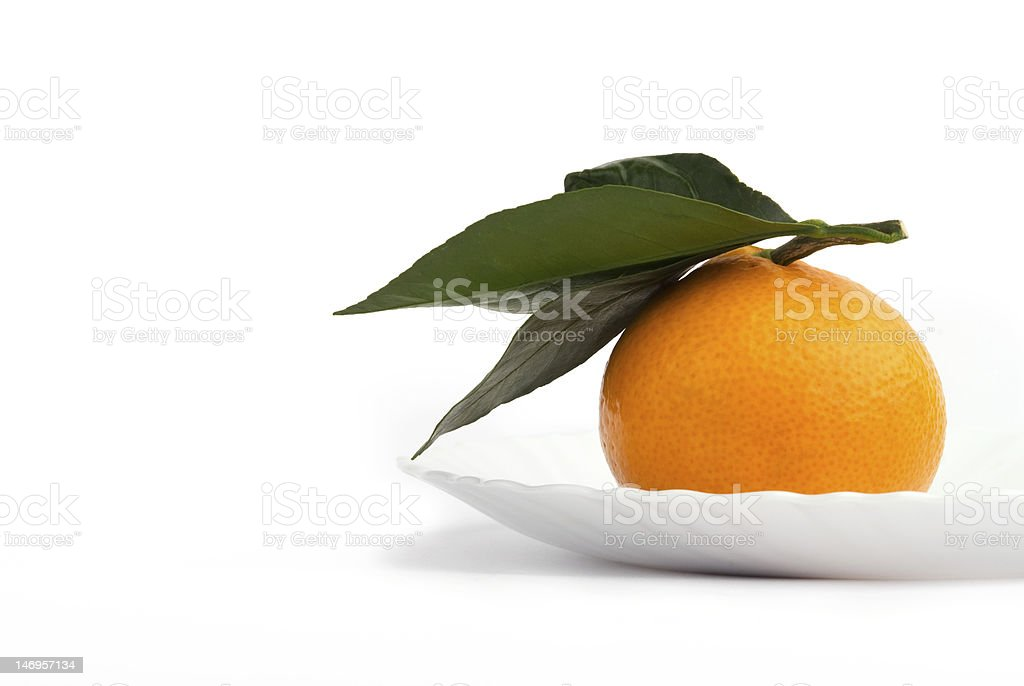 One tangerine on a plate royalty-free stock photo