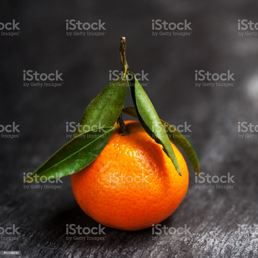 One tangerine with leaf on a black stock photo