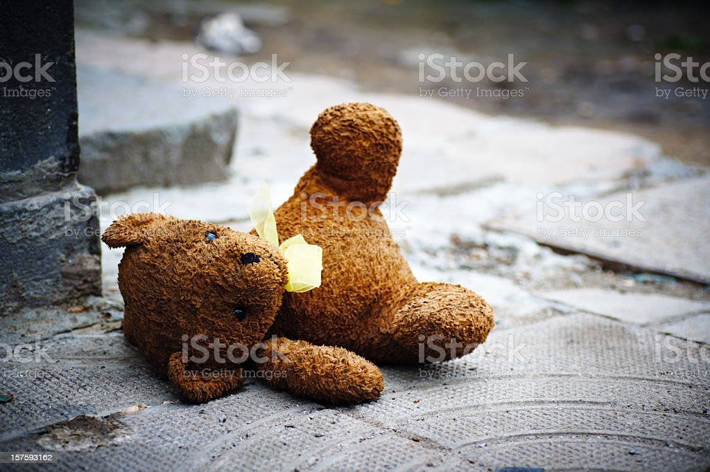 One teddy bear laying in the ground stock photo