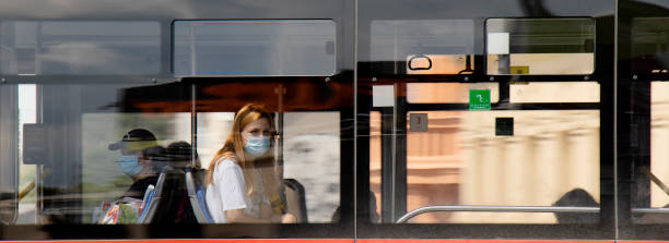 One teen woman wearing face surgical mask riding on window seat of a public bus