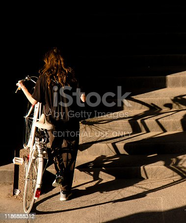 812812808istockphoto One teenage girl in black pushing the white bike up the public stairs in sunlight and shadows 1186888312