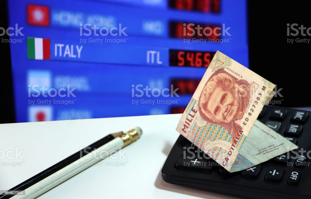 One thousand Lire of Italy banknote on the calculator with pencil on white floor with digital board of currency exchange money background. royalty-free stock photo