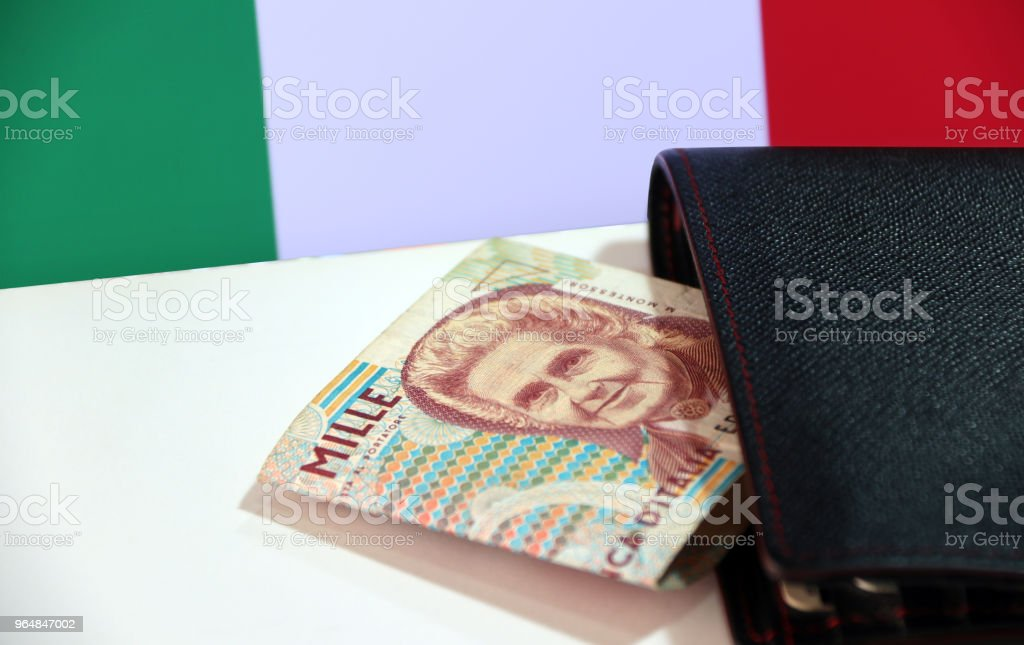 One thousand Lire of Italy banknote with black wallet on the white floor with Italia flag background. royalty-free stock photo