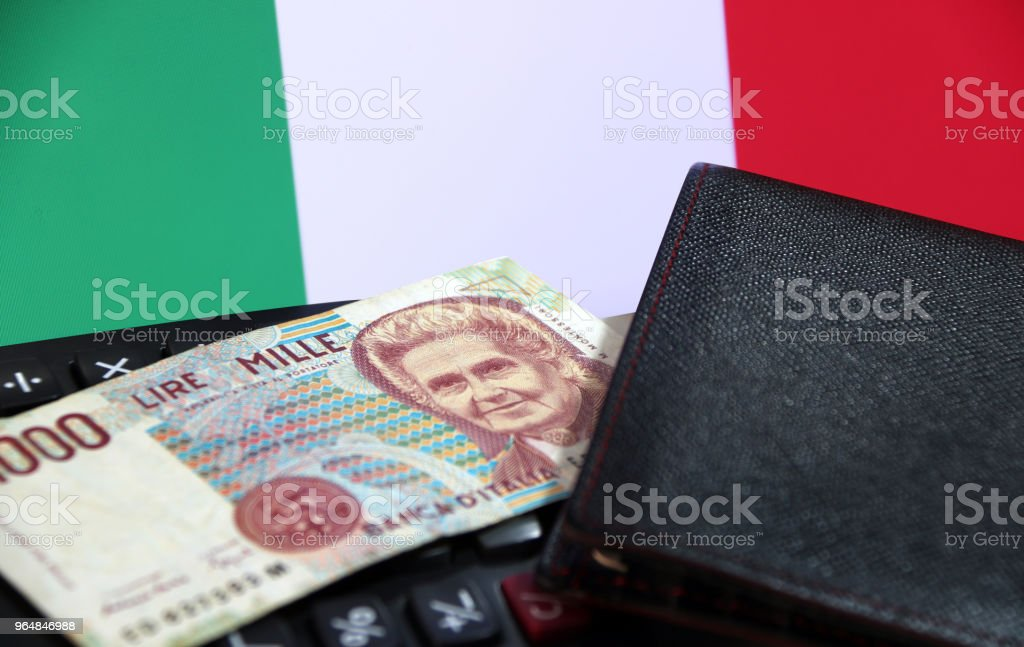 One thousand Lire of Italy banknote with black wallet on the calculator with Italia flag background. royalty-free stock photo