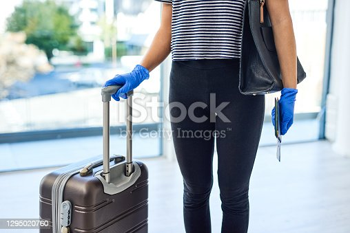 Shot of an unrecognisable gloved woman carrying her passport and ticket in an airport