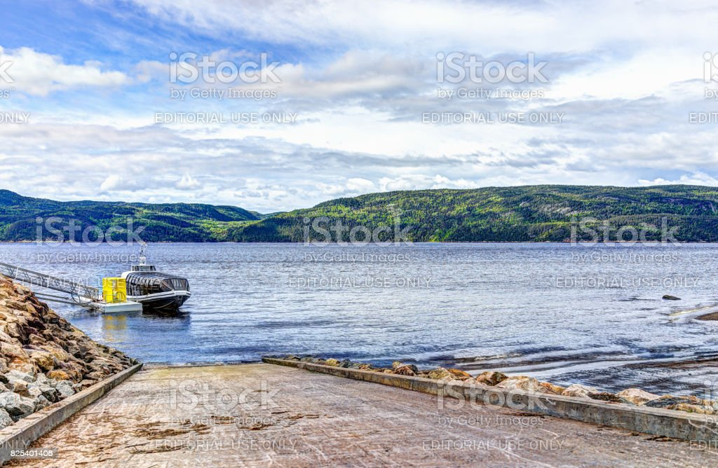 One tour boat in harbor in Quebec village by Saguenay fjord river stock photo