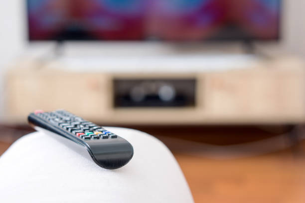 One TV remote control on the armrest of sofa stock photo