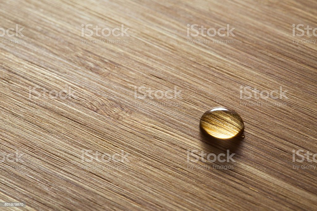 One water drop on a wooden surface, closeup stock photo