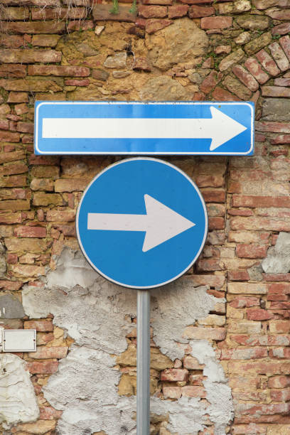 one way and turn right street sign on a wall stock photo