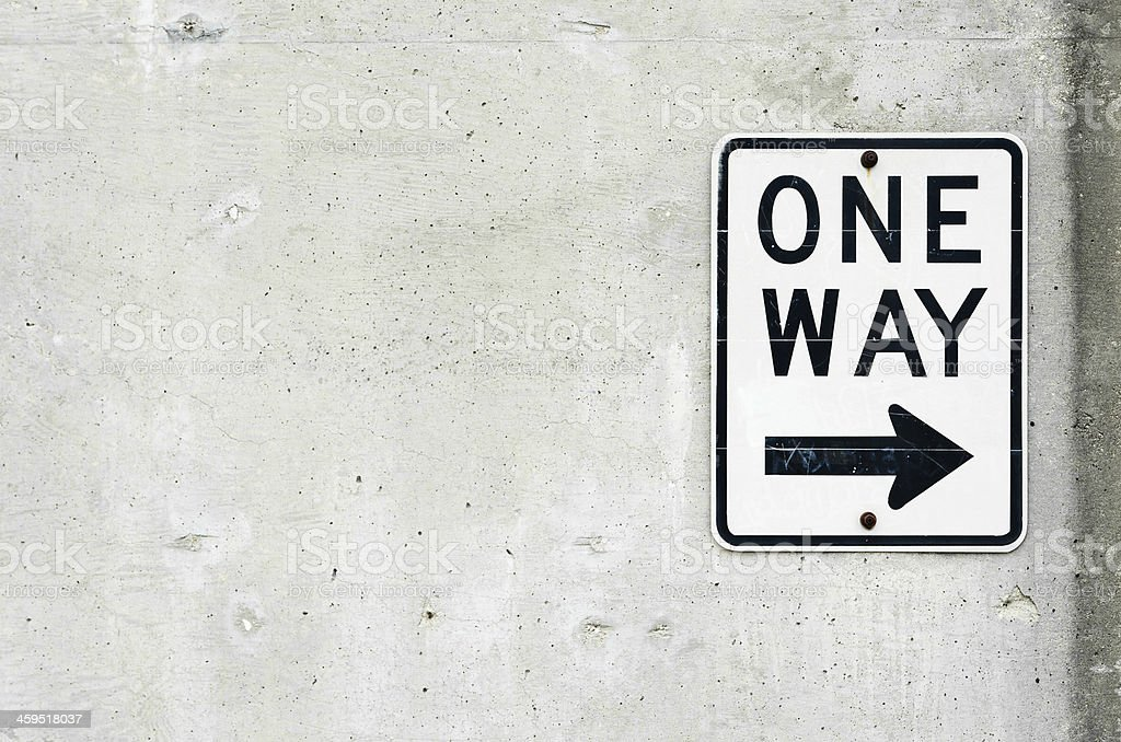 One way sign on concrete wall stock photo