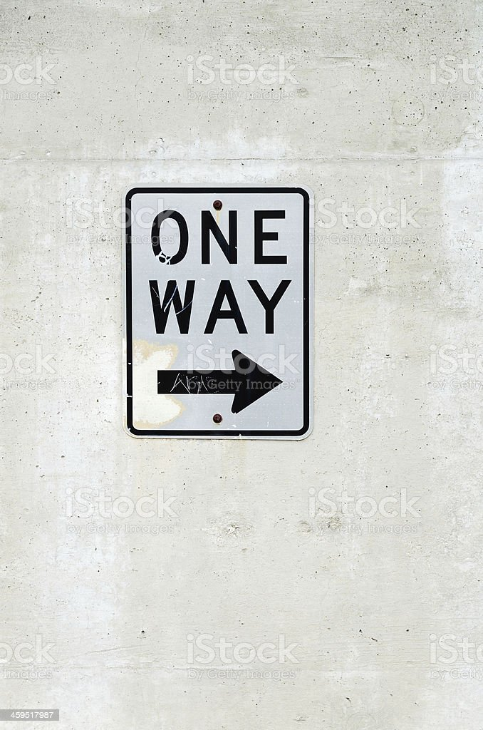 One way sign posted on concrete wall stock photo