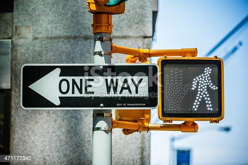 One way traffic sign beside green pedestrian traffic light on the street of New York City, Manhattan, USA.