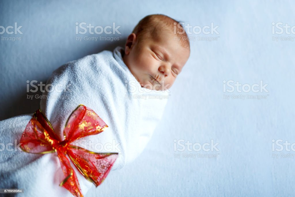 One Week Old Newborn Baby Sleeping Wrapped In White Blanket With Red