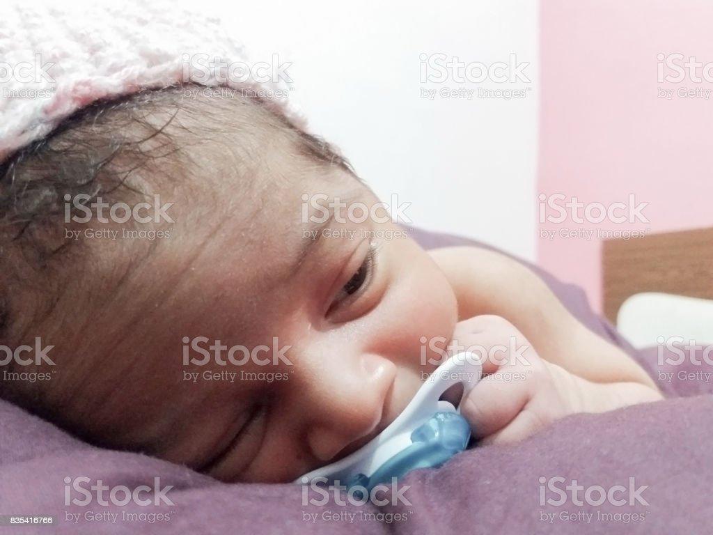 one week old newborn baby with dummy stock photo