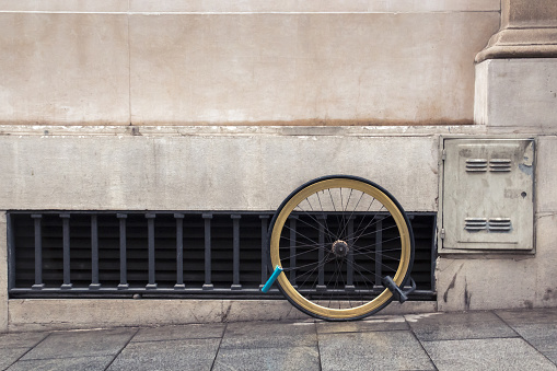 One wheel of a bicycle chained by two locks to the facade of the house, the concept of the problem of theft of bicycles in the city