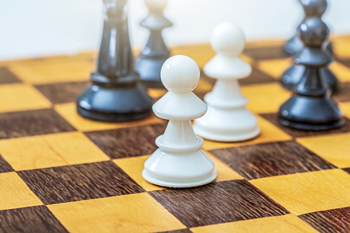 One white pawn on chessboard among other chess pieces. Concept of success business strategy and leadership