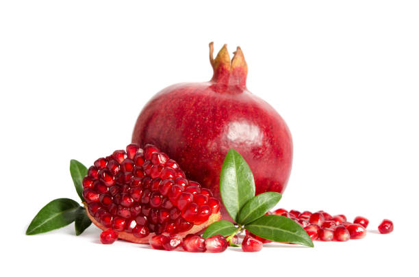 one whole and part of a pomegranate with pomegranate seeds and leaves isolated on white background - romã imagens e fotografias de stock
