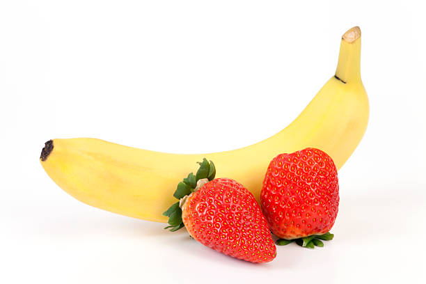 One whole banana and two whole strawberries stock photo
