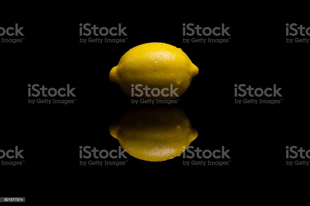 One whole isolated yellow lemon on black background photo libre de droits