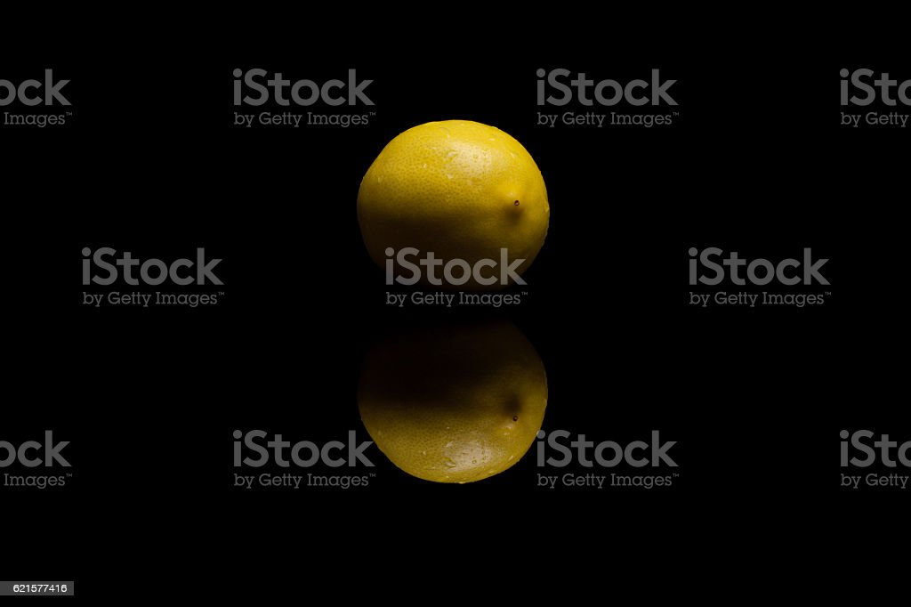One whole isolated yellow lemon with watter drops on black photo libre de droits