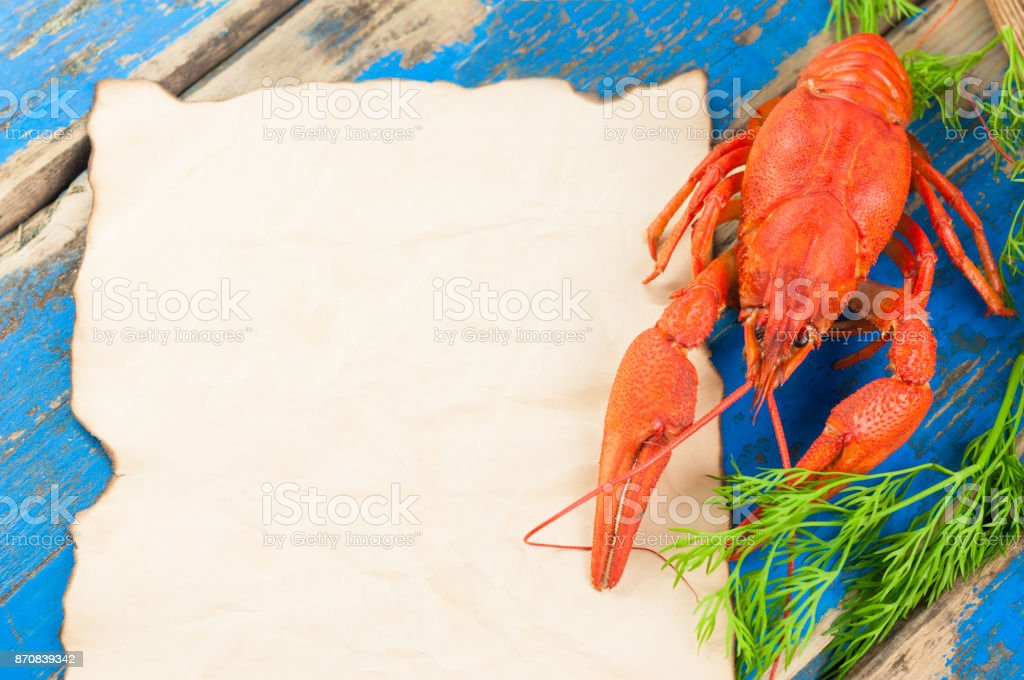 One whole red boiled crawfish with twig of green fresh dill near empty roasted sheet on old rustic blue wooden planks stock photo