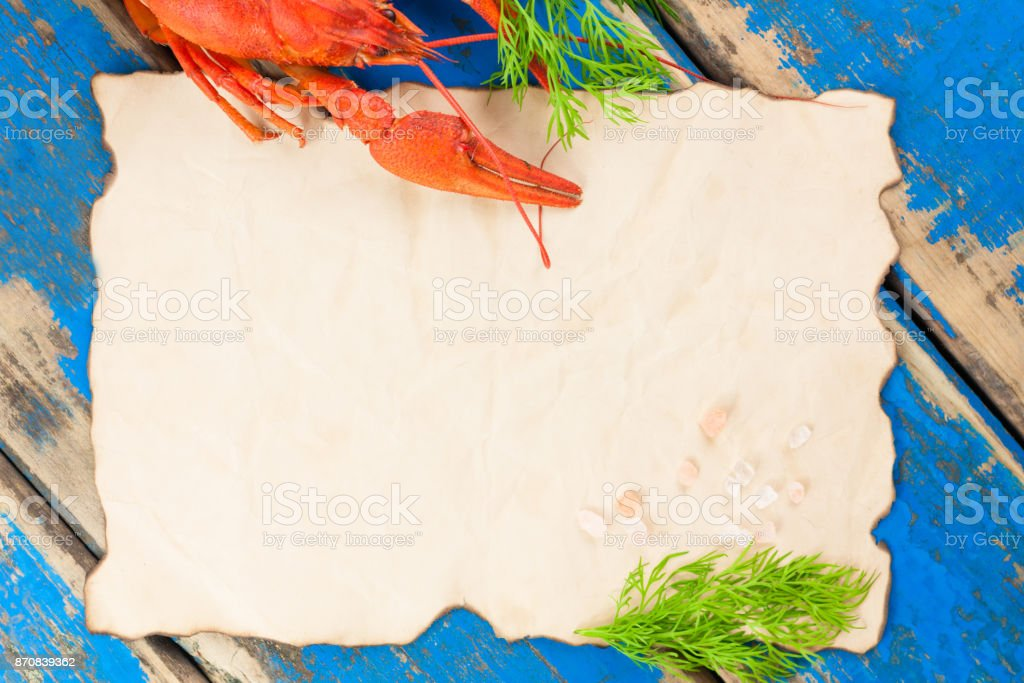 One whole red boiled crawfish with twig of green fresh dill near empty roasted sheet with salt on old rustic blue wooden planks stock photo