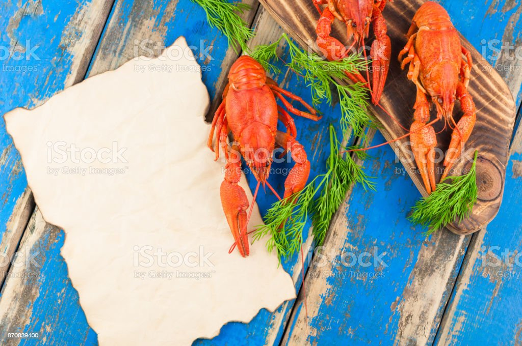 One whole red boiled crayfish beside many crawfish on brown cutting board and fresh green twigs of dill near empty roasted sheet on old rustic blue wooden planks stock photo