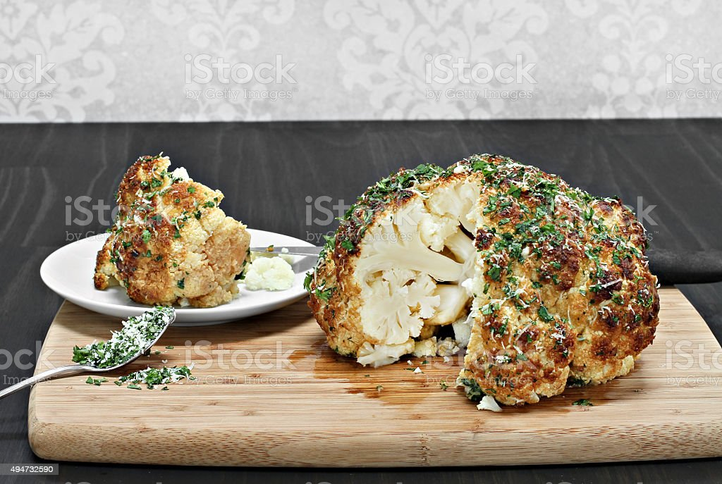 One whole roasted cauliflower head with a slice removed. stock photo