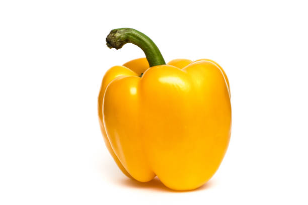 One whole Yellow Pepper up close on white background. Isolated pepper, yellow with green stem. Stem located outside frame. Full pepper visible. yellow bell pepper stock pictures, royalty-free photos & images