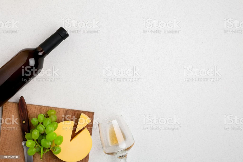 One wine glass with white wine, bottle of white wine, cheese on white background. Horizontal view from the top stock photo
