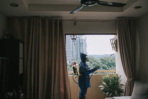 One woman in protective suit spraying and disinfecting the balcony exterminator pest control virus