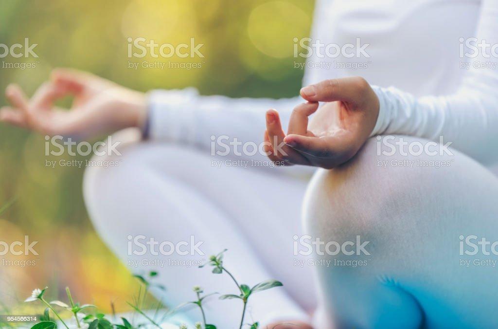 Eine Frau ist als Teil des Yoga im Park meditieren. Health Management Concepts.this Bild weich konzentriert. – Foto
