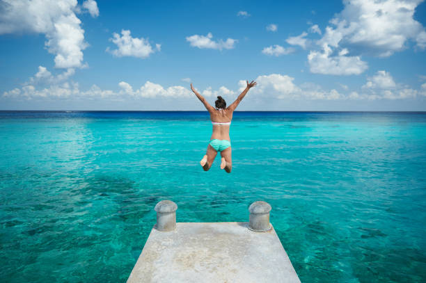 One woman jump in blue water stock photo