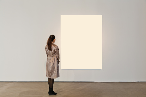 One woman looking at white frame in an art gallery
