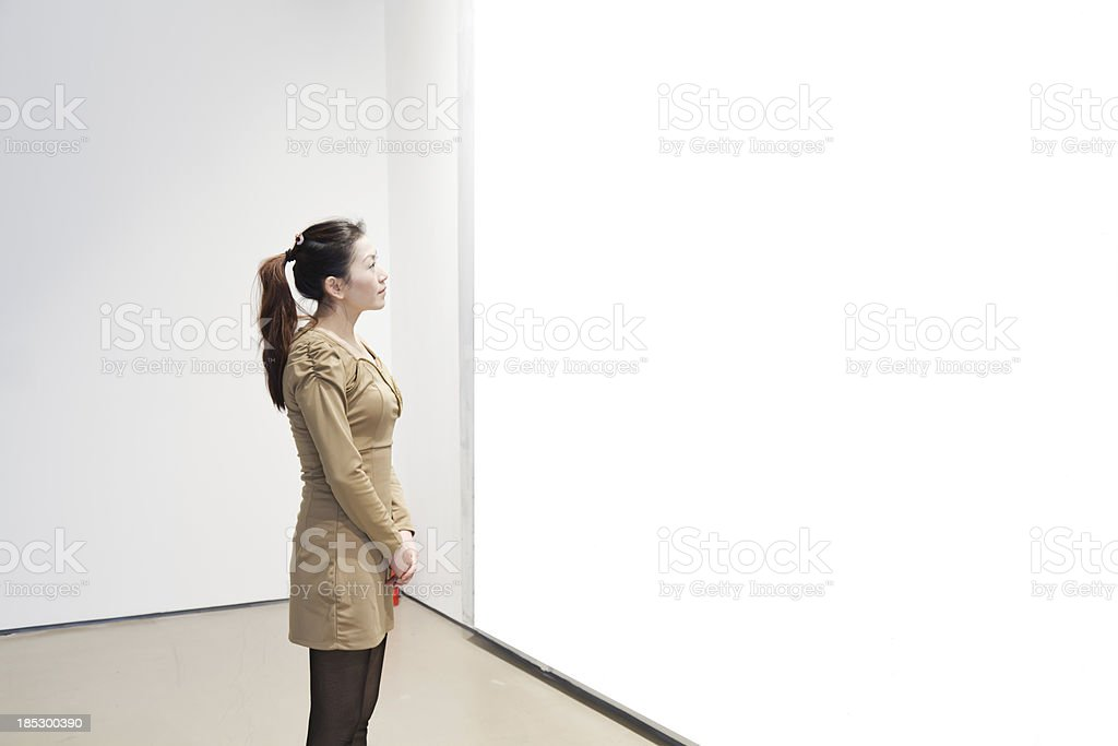 One woman looking at white frame in an art gallery royalty-free stock photo