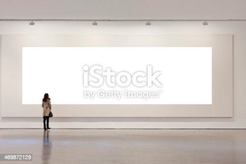 istock One woman looking at white frame in an art gallery 469872129
