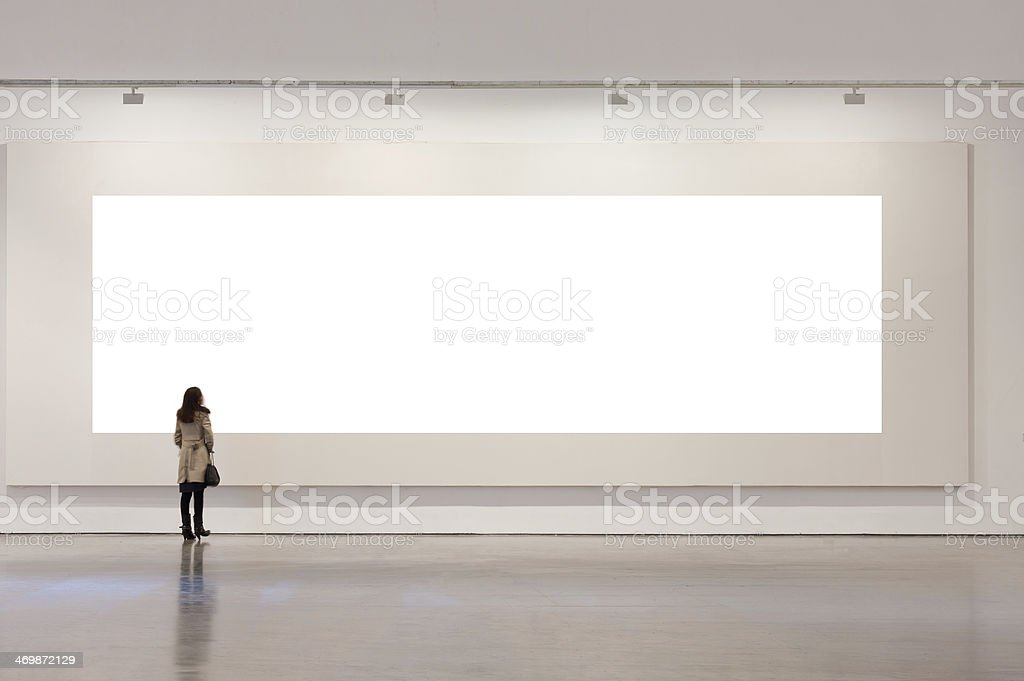One woman looking at white frame in an art gallery stock photo