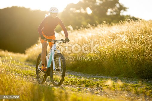 athletic sportive fit 44 years old woman cycling on electric mountainbike on path between high dry grassland on sunny summer afternoon in backlight