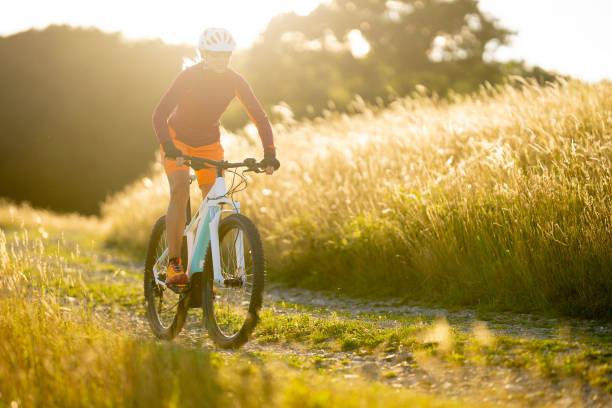 eine frau auf elektrische sommer sonnenschein kulturlandschaft mountainbikestrecke - elektrorad stock-fotos und bilder