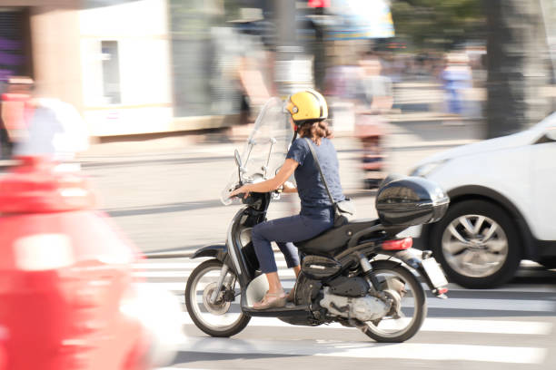 One woman riding a vespa scooter in the city street traffic