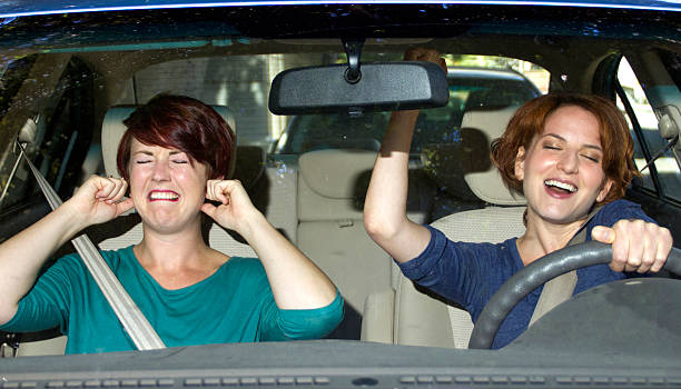 One woman singing and one woman covering her ears in a car stock photo