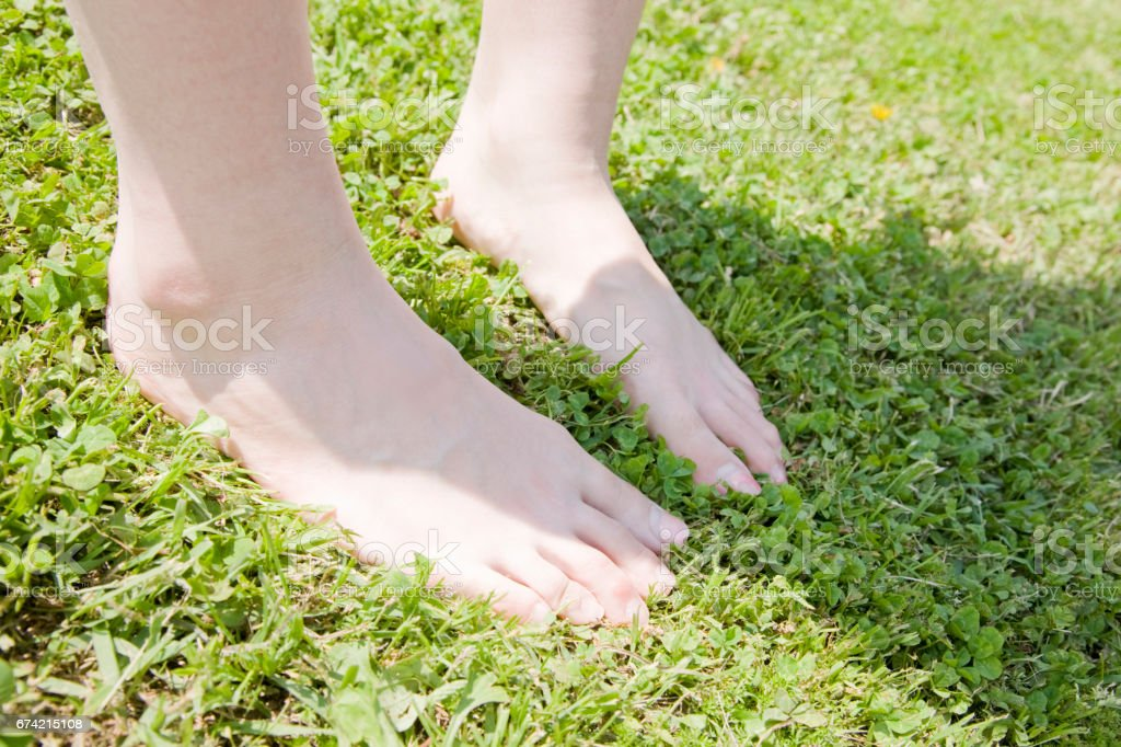 One woman stands barefoot on the lawn stock photo