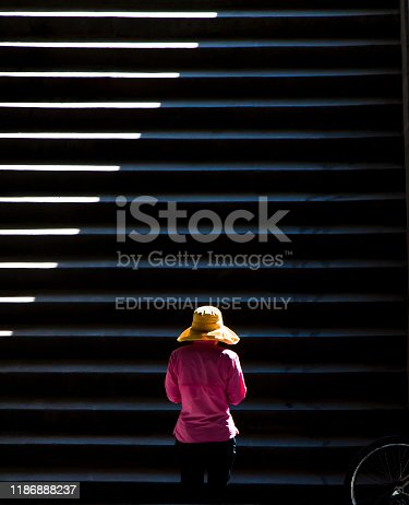 812812808istockphoto One woman wearing yellow hat walking up the public stairs in sunlight and shadows 1186888237