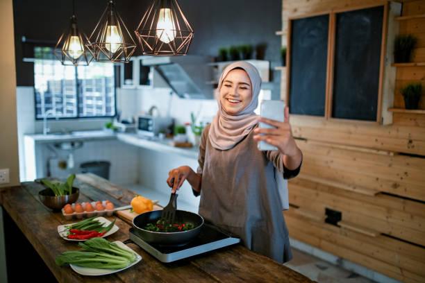 una mujer que mira el teléfono mientras cocina - ramadán fotografías e imágenes de stock